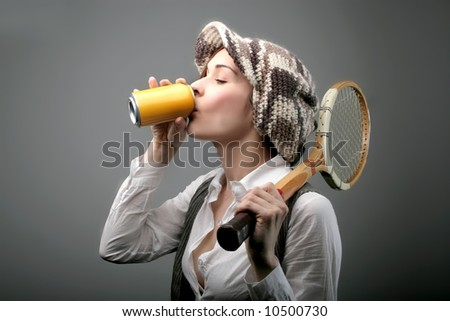 a young woman with a  Aluminum Drink and a racket - stock photo