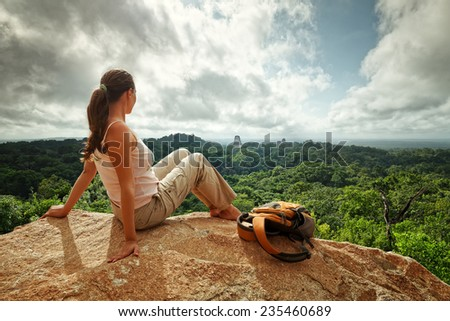 A young woman with a backpack is looking at the ruins of an ancient Maya city Tikal. National park Tikal. Guatemala - stock photo