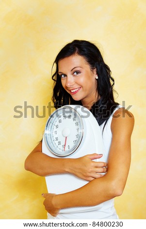 a young woman with a balance in his hand smiling after a successful diet - stock photo