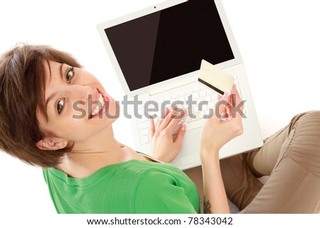 A young woman with a laptop and a credit card, from above - stock photo