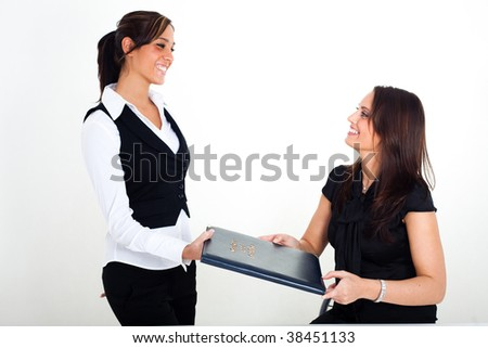 A young woman with a menu card in her hands, and a waitress next to her - stock photo