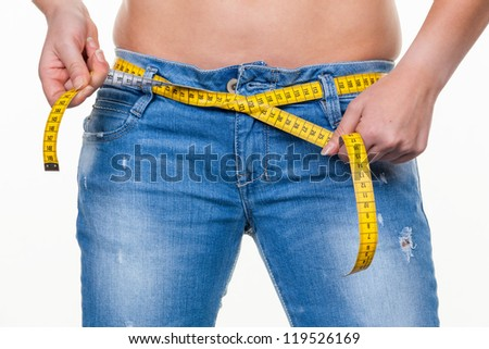a young woman with a tape measure before the next diet. removing fast and - stock photo