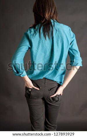 A young woman with a teal silk blouse on and hands in back pockets of tight pants. - stock photo
