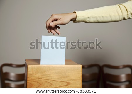 a young woman with a voter in the voting booth. voting in a democracy - stock photo