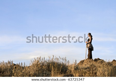 A young woman with a walking stick observes her surroundings from the top of a hill