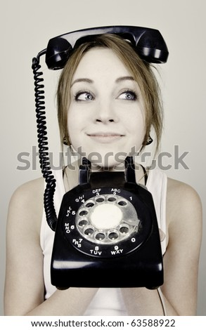A young woman with an antique telephone on her head - stock photo