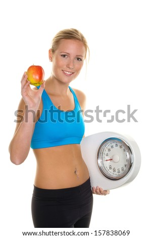 a young woman with an apple and a scale. symbolic photo for and remove, as well as healthy eating - stock photo