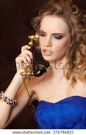 A young woman with blond curly hair in a blue dress holds an antique handset.