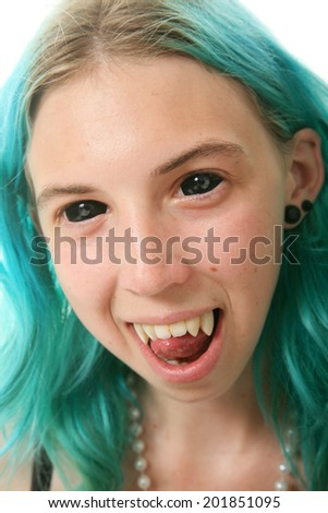 A young woman with blue hair wears black contact lenses and her Vampire Fangs. Isolated on white with room for your text  - stock photo