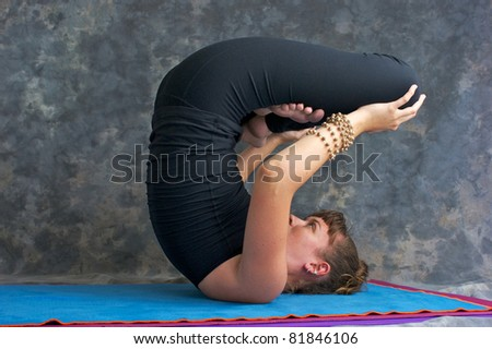 A young woman with brown hair is doing advanced yoga asana Urdhva-Padmasana or Upward lotus. - stock photo