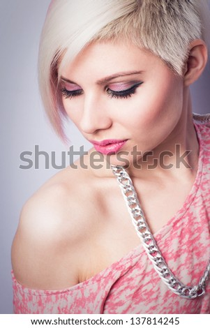 A young woman with creative hair style and a 1980s look. Pink toned. - stock photo
