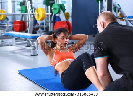 A young woman with her coach at the gym