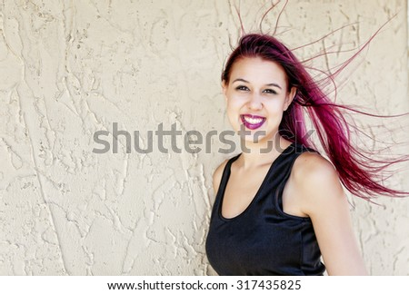 A young woman with her hair dyed magenta pink, blowing in the wind. - stock photo