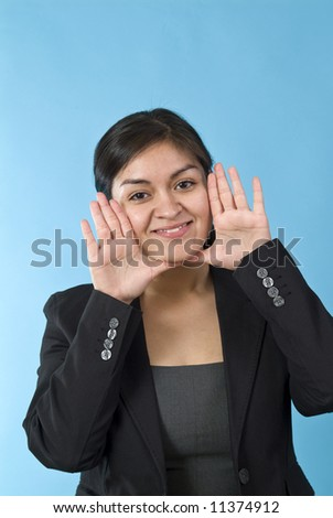 A young woman with her hands up to her face as if ready to call out to someone. - stock photo