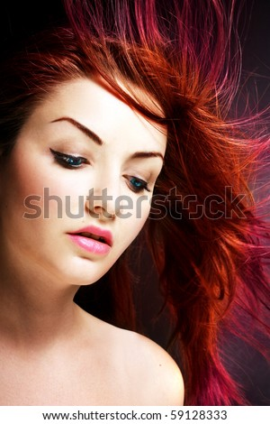 A young woman with her multicolored hair blowing in the wind. - stock photo