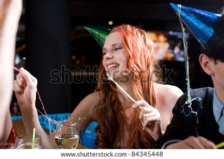 A young woman with long red hair amidst a celebration, wearing a party hat and covered with streamers. - stock photo