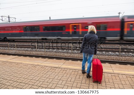 a young woman with luggage waiting on the platform of a railway station for their train. train delays - stock photo