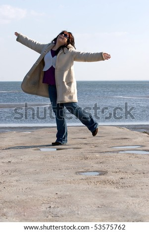 A young woman with red highlights dancing on the jetty at the beach. - stock photo