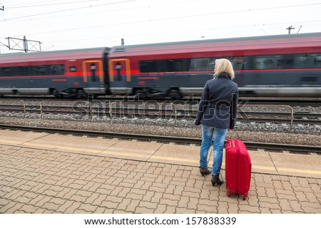 a young woman with suitcase waiting on the platform of a railway station on their train. train delays - stock photo