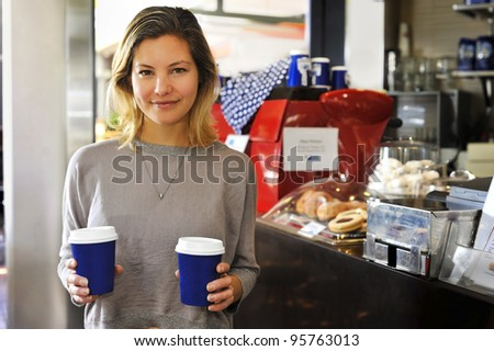 "a young woman with takeaway coffees. This model has a lovely natural ""everyday"" look. - stock photo"