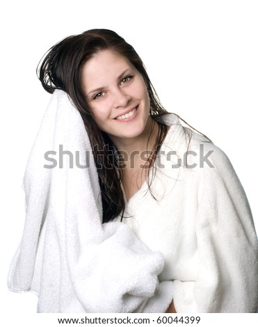 A young woman with wet hair in white robe toweling off after a shower.