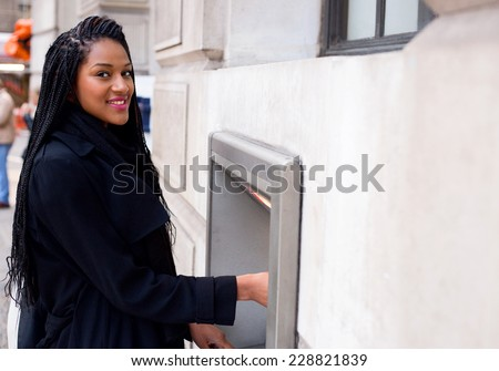a young woman withdrawing cash  - stock photo