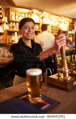 A young woman working behind a bar looking to camera - stock photo