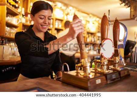 A young woman working behind a bar preparing drinks - stock photo