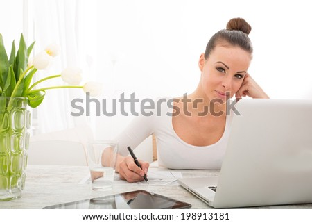 A young woman working from home with a laptop computer. - stock photo