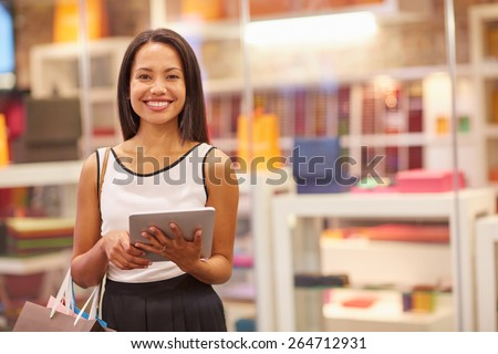 A young woman working on her digital tablet while standing in a mall - stock photo