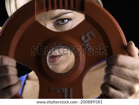 A young woman working out in a gym peers through a weight. - stock photo