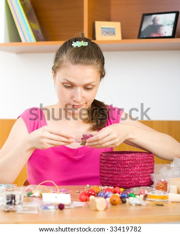 A young woman working with her beads, picking the right one for her creation. - stock photo