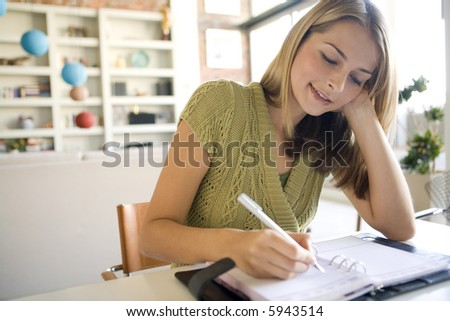 A young woman writing in her agenda - stock photo