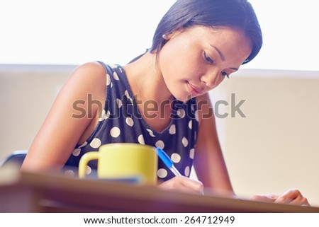 A young woman writing while sitting in her office - stock photo