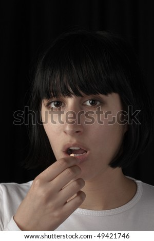A young women taking one pill - stock photo