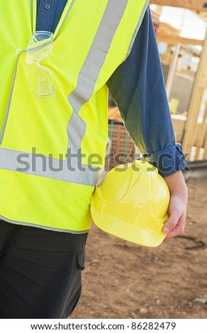 A young worker at the construction site with safety equipment - stock photo
