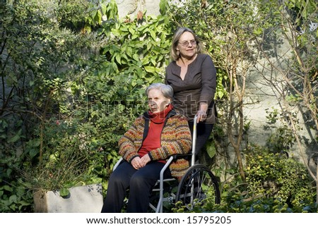 A younger woman is with her elderly mother in a garden.  She is pushing her wheelchair, smiling, and they are both looking away from the camera.   Horizontally framed shot. - stock photo