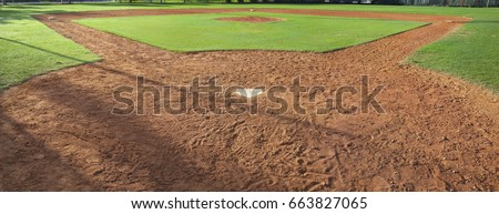 A youth baseball field viewed from behind home plate in morning light
