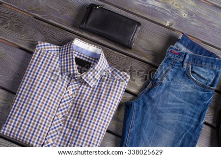 A youth checkered shirt with jeans and purse. - stock photo