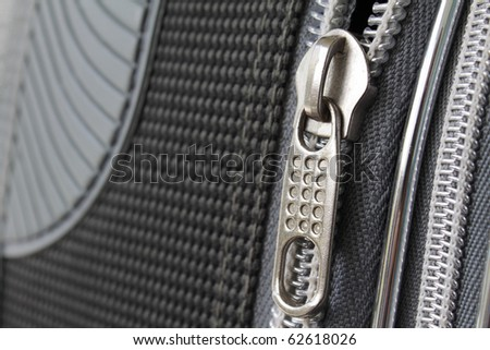 A zipper on grey suitcase closeup photo