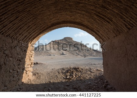 A zoroastrian Tower of Silence atop a hill framed by an old building in the persian city of Yazd, Iran.