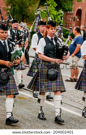 AABENRAA, DENMARK - JULY 6 - 2014: Scottish bagpipe band is marching down the street at the annual tilting festival in Aabenraa - stock photo