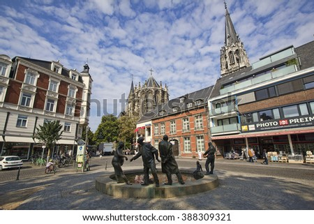 Aachen, Germany - August 28, 2013: Small square in the centre of Aachen with people shopping, a fountain and sculptures and towers of the cathedral in background in Aachen, Germany on August 28, 2013