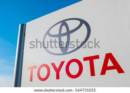 AACHEN, GERMANY JANUARY, 2017: Toyota dealership sign against blue sky. Toyota is the world's market leader in sales of hybrid electric vehicles.