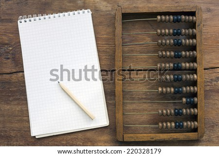 abacus and notes on the vintage wooden table  - stock photo