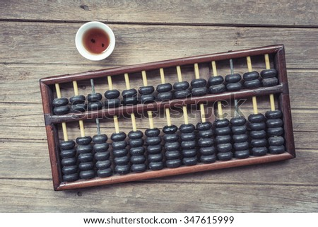 Abacus on the wooden background with few small tea cup. Top view concept.