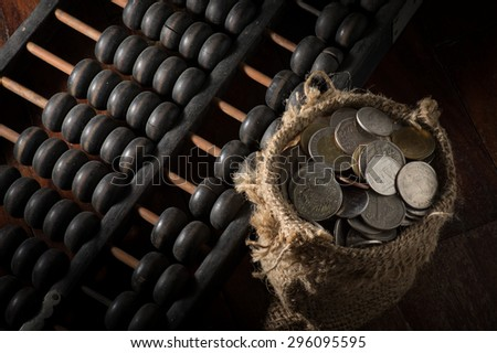 Abacus with coins in gunny sack. - stock photo