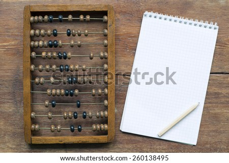 abacus with notepad and pencil on vintage wooden table - stock photo