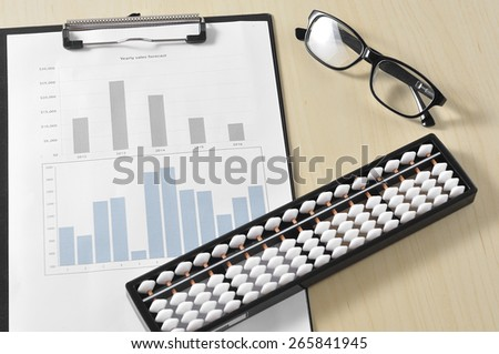 Abacus With Yearly graph and Eye Glass, Finance Concept and Selective Focus - stock photo