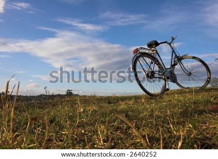 abadoned bicycle on green grass - stock photo